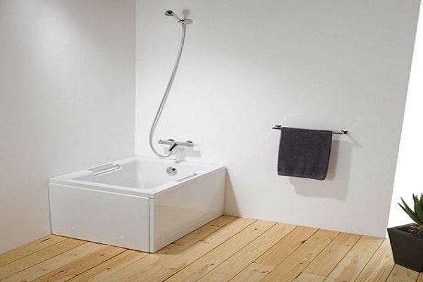 Une baignoire sabot carré discrète dans la salle d'eau.