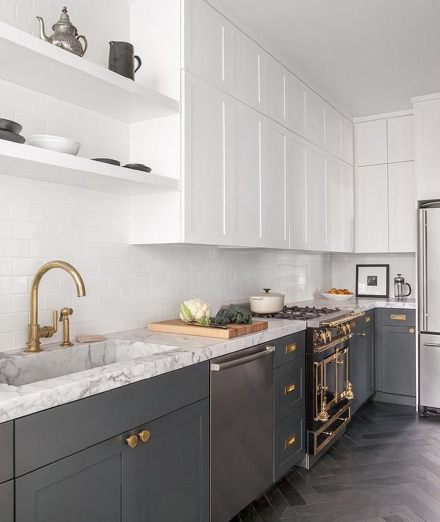 Beautiful white and gray contemporary kitchen boasts gray herringbone floor tiles complementing charcoal gray shaker cabinets accented with aged brass knobs and vintage inset pulls and fitted with a stainless steel dishwasher and a La Cornue Range.