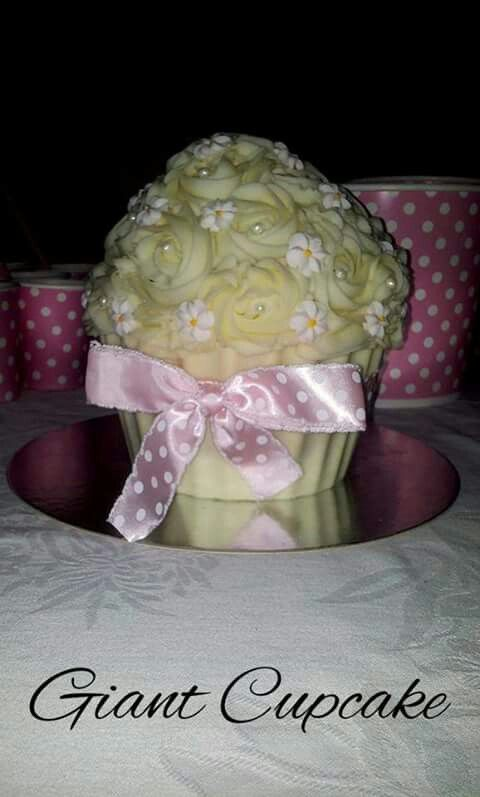 Giant cupcake cake.  Vanilla cake with a hard white chocolate base, cream cheese frosting topped with little flowers and sugar balls. Perfect for any little girls party.   Check us out at www.facebook.com/totaleventplanning