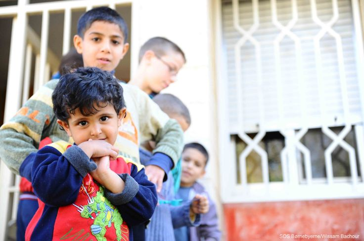 Boys standing in front of house in Damascus #Syria. SOS Children's Villages help internally displaced children and families in Syria with food supplies, shelter and warm clothes.
