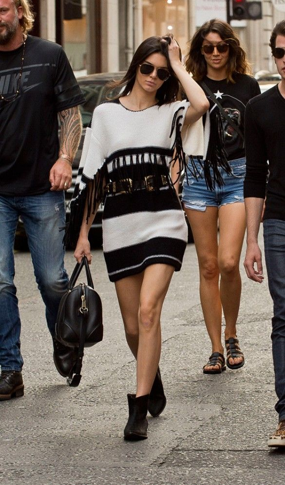 Kendall Jenner pairs a sweater dress with fringe sleeves with booties, belt and structured bag.