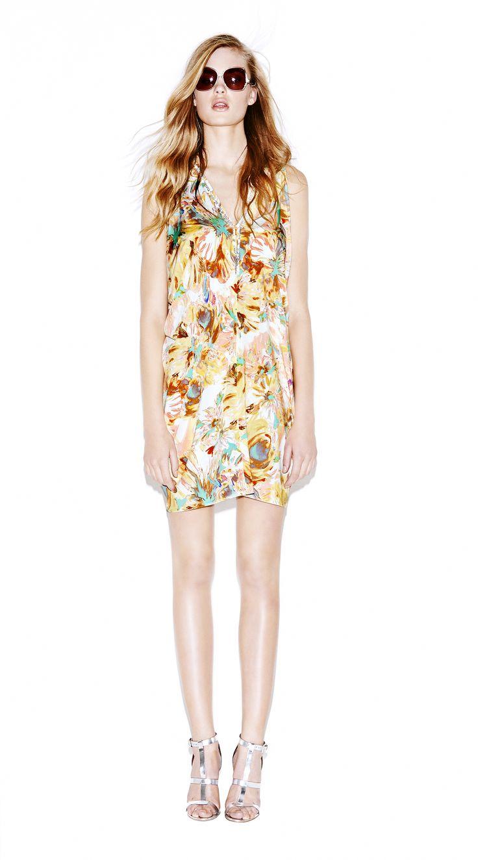 Model wears Naughty Dog stretch flower print mini dress, draped on both sides; Swarovski elements decorate the V neckline.