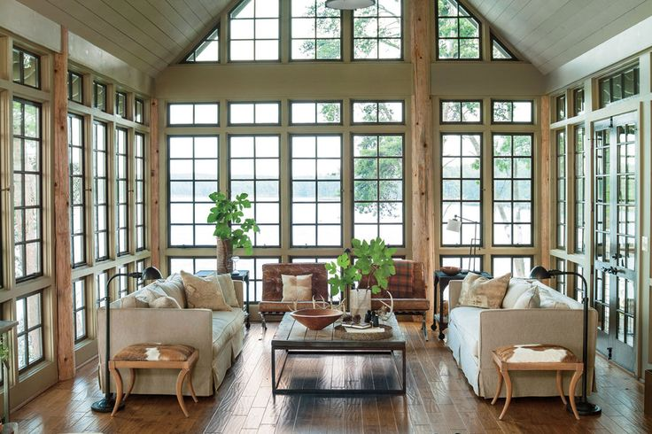 Keep the beautiful views the primary focus. A neutral palette devoid of area rugs or window treatments camouflage this lake house living room with its surroundings.  See more of this Lake House in the Trees