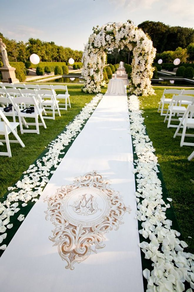 A sophisticated, monogrammed aisle runner is the perfect accent to the petal aisle and heavily decorated floral arch.