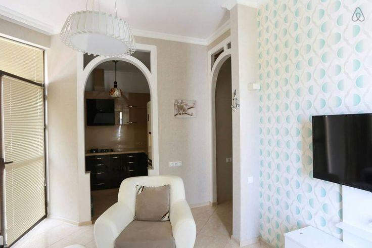 Очень светлая гостиная с телевизором, раскладным диваном и двумя креслами. Диван на 2 спальных места. Обогрев пола, плитка. Жалюзи и плотные шторы, если вы любите приглушенный свет. Студия, но кухня визуально отгорожена. 2 балкона.