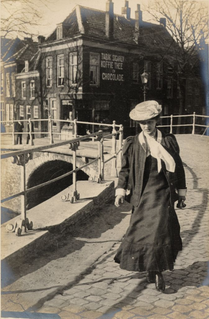 Holland in April 1906. An excellent view of a woman crossing over one of the canals and below, more tall windows, traditional costume and curious glances.
