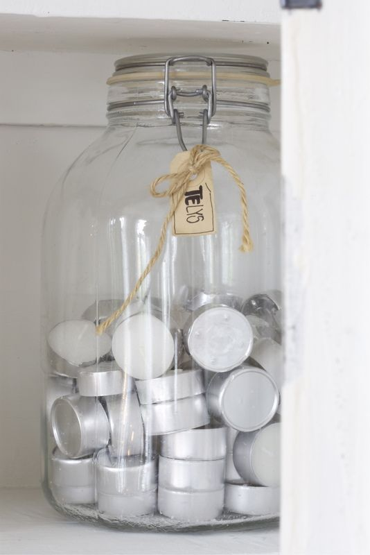 tealights stored in a jar with raffia.  Cute.  I store my candles in my dining room buffet.  Maybe I'll move them to my hutch when I display them like this.