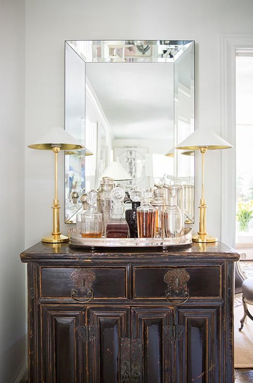 A silver serving tray flanked by a pair of lamps transforms an antique cabinet into an elegant bar | domino.com