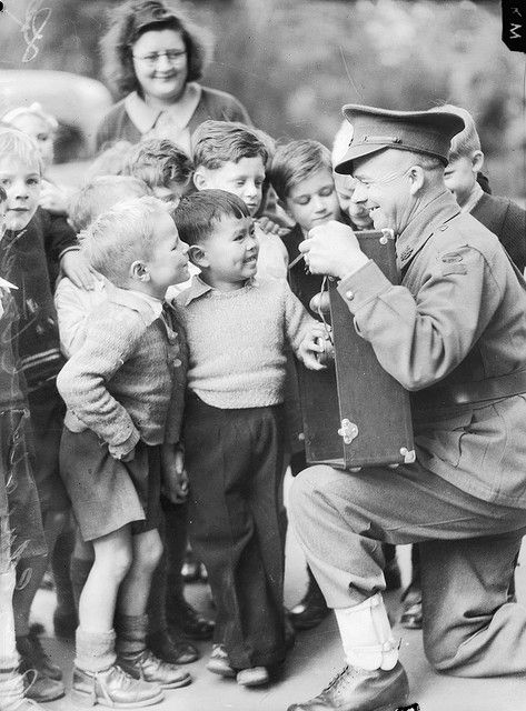 1942: Private Jack Martin, driver of the Mobile Entertainment Unit purchased with money raised by the State School children of Victoria, shows children of the Rathdown Street State School, Carlton, the workings of a loud speaker. Melbourne, Australia.