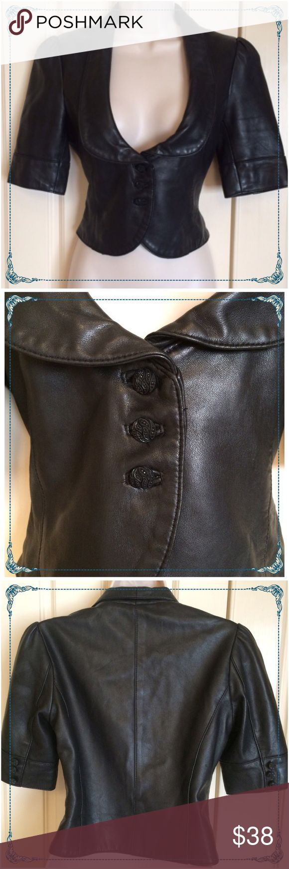 """Plunging leather top steam punk or rocker chique Buttery soft black Marciano plunging neck line genuine leather top. Adorned with jet black braided buttons on the front & the sleeves. An exquisite piece that's  very flattering to your figure. One small scratch on the back of the top but very unnoticeable. Size small. measuring 17""""  long x 27"""" waist  34"""" chest. Marciano Tops"""