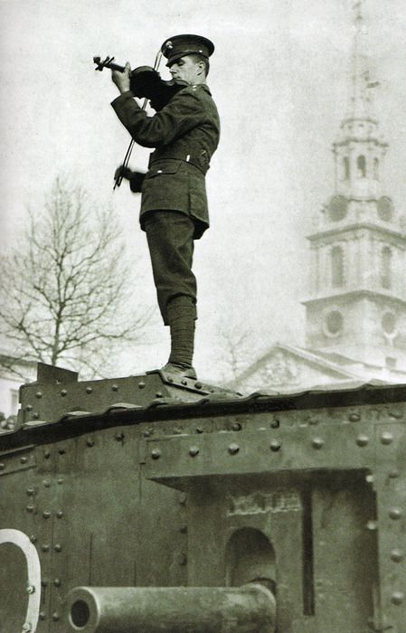 Soldier playing the violin on a tank. WWI