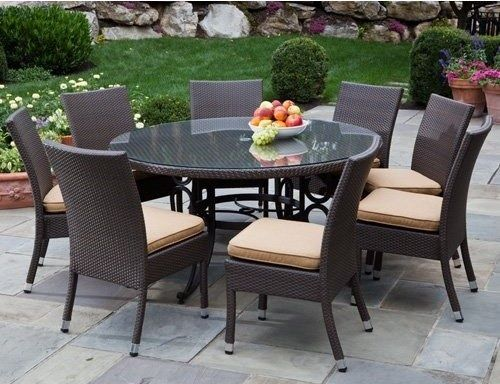 Wicker patio furniture with glass round patio table on top and ...