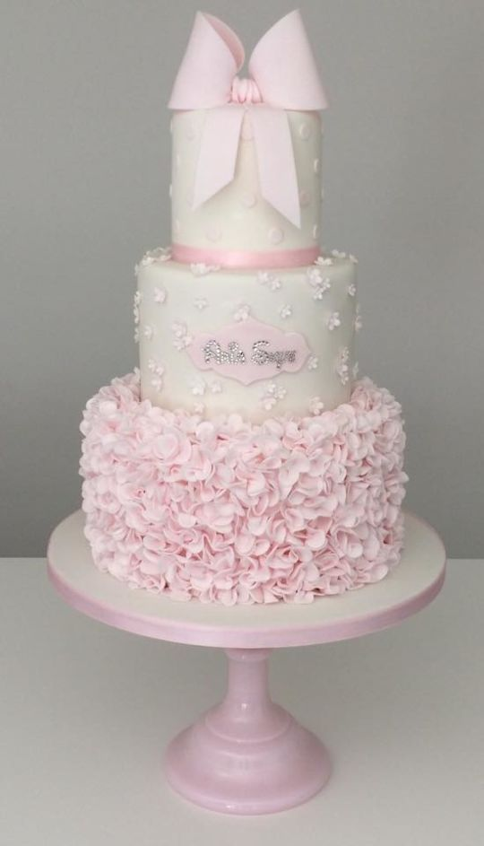 This three tier christening cake in delicate pink and white, features ruffles, blossoms, polka dots and a touch of sparkle, topped with an icing bow