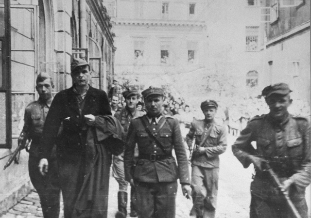 Convicted war criminal Amon Goeth is escorted by Polish guards to the courthouse in Krakow for sentencing.  Amon Leopold Goeth (1908-1946), a native of Vienna, joined the Nazi party in 1932 and the SS in 1940. During the war he was sent first to SS headquarters in Lublin and subsequently to Krakow. From February 1943 until September 1944 Goeth held the position of commandant of Plaszow. After the war he was extradited to Poland, where he was tried, sentenced to death and executed in 1946.