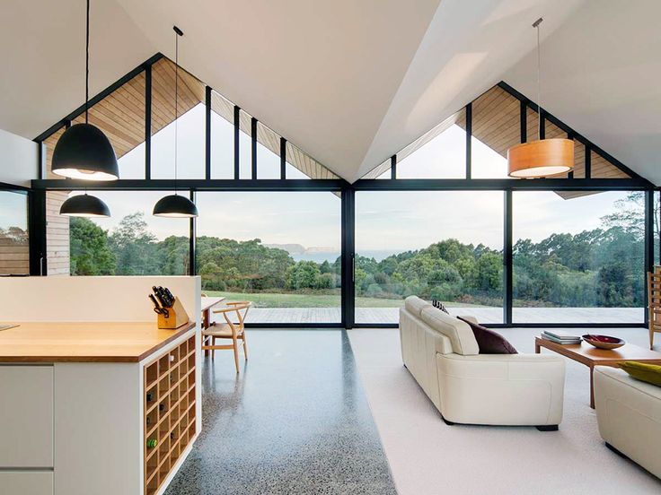 Australian architecture firm Room11 have completed a contemporary house in Port Arthur, Tasmania, which has been designed around the stunning views of the Tasman Island and the Southern Ocean beyond. Inspired by the traditional form of a farmhouse, the main living space features floor to ceiling windows across an entire side, which simultaneously flood the space with light and place a focus on the landscape outside.