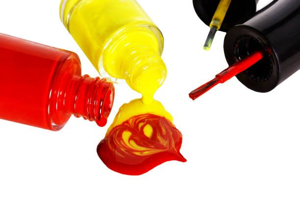 red and yellow nail polish is open mixed spilled drops