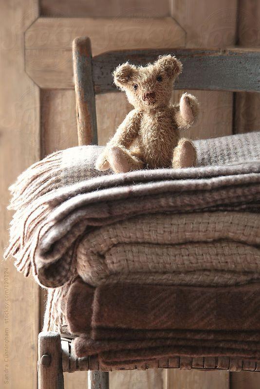 Small teddy bear on chair with wool blankets by Sandra Cunningham