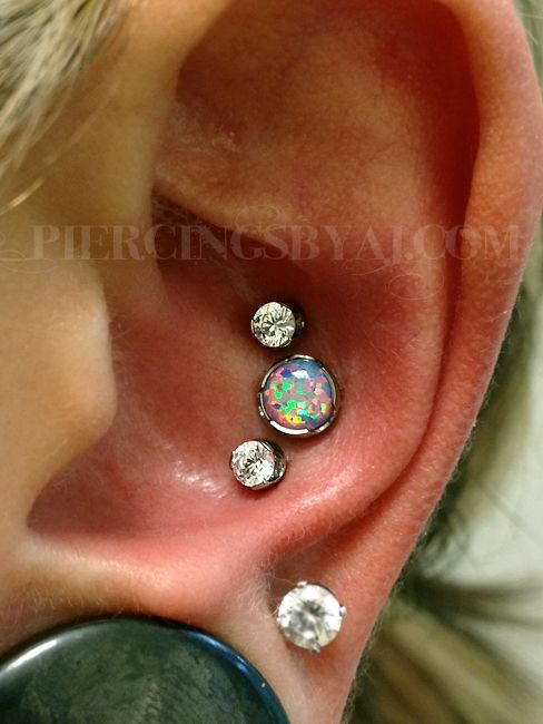 Fresh triple conch I got to do last night. This piece features one 14g labret stud with 5mm prong set light purple opal and two 16g labret studs with 3mm prong set white CZ gems. Jewelry from Anatometal.