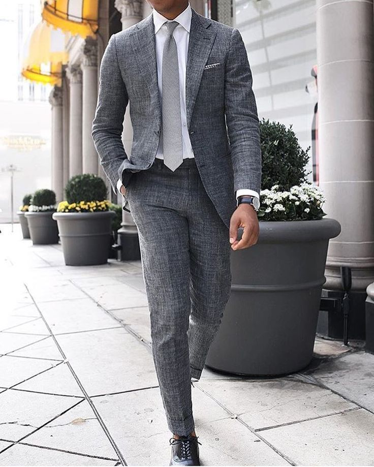 Try teaming a grey suit with a white classic shirt for a sharp classy look. Why not introduce black leather oxford shoes to the mix for an added touch of style?   Shop this look on Lookastic: https://lookastic.com/men/looks/suit-dress-shirt-oxford-shoes/21600   — White Dress Shirt  — Grey Tie  — White and Black Gingham Pocket Square  — Grey Suit  — Black Leather Watch  — Black Leather Oxford Shoes