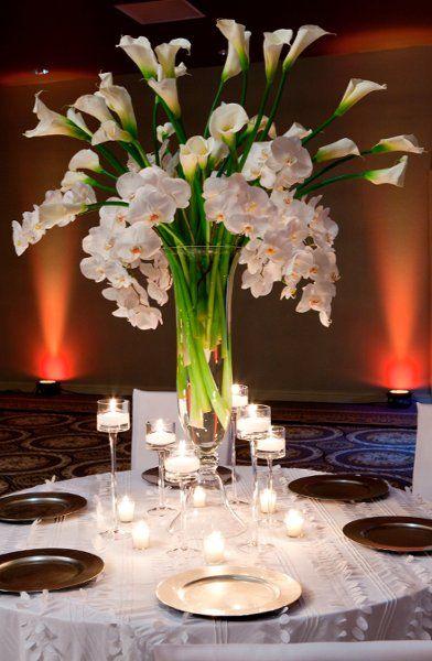 Centro de mesa de jarrón alto con cartuchos y orquídeas. #CentrosDeMesa #DecoracionBodas