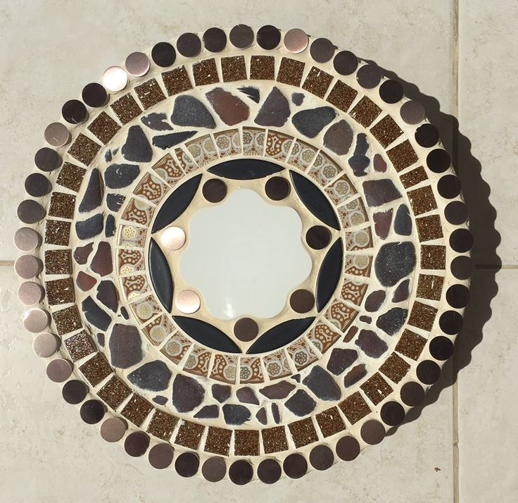 """This stone is called """"Amber Dawn"""" and now resides in Crane Gardens, Barbados.  It has a fun centerpiece that I cut out of a white dinner plate.  Next comes copper button tiles and black marquise ceramic tiles.  I then added pieces cut from an exquiste 1950s East German plate in shades of gold and copper.  Next came a ring of brown beer bottle sea glass found on the island, a ring of glass tiles that have an oatmeal texture and a full ring of copper button tiles to finish off the last ring."""