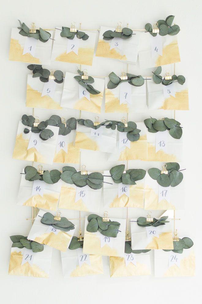 Adventskalender selber machen, DIY-Idee mit Eukalyptus und weiß-goldenen Papiertüten. Den fertigen Adventskalender einfach mit einem Deko-Gitter an der Wand anbringen inkl. Ikea Hack.