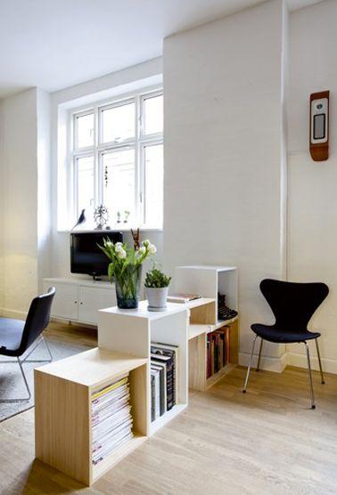 Des caissons bois stratifié blanc et couleur chêne clair pour ranger livres et bibelots.astuce qui servent aussi à séparer l'espace du salon...