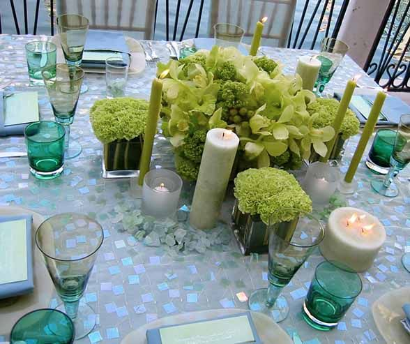 An iridescent blue and teal tablecloth, topped with green carnations, cymbidium orchids, lime green candles and bits of sea glass, evokes the colors of the sea.