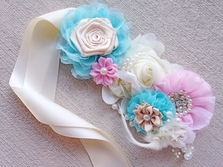 This maternity sash is the perfect addition to your beautiful maternity pictures! Adorned with gorgeous fancy flowers, all set on a satin ribbon, you simply tie it around your belly bump for the finis