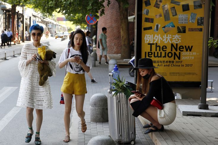 """A poster in a Beijing arts district reads """"the new normal."""" China's new credit rating..."""