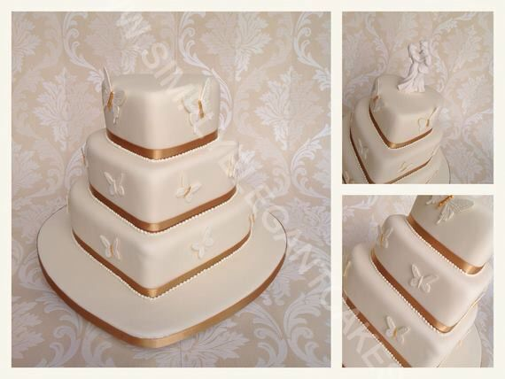 A beautiful Ivory heart shaped wedding cake with Ivory & gold butterflies.