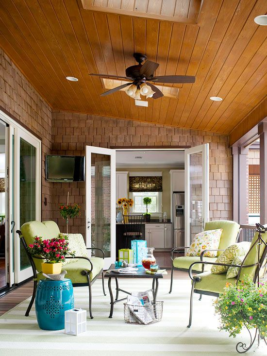 a fabulous covered patio layered with colorful furnishings and blooming plants (oh and a flat screen TV too)  :)