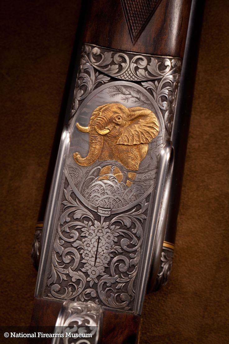 This early 20th Century elephant gun features vine and scroll engraving with heavy relief gold inlaid elephant on both sides and the bottom of the frame.  It came in an original case, complete with a bottle of Rangoon Oil.