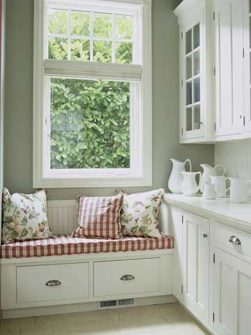 Add a soft touch to a storage area off the kitchen with an upholstered cushion on a bench. A window seat is a great way to add a punch of color to a mostly white space.  West end of kitchen with cabinets all the way down.