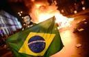 Un manifestante porta la bandera de Brasil frente a una de las hogueras que se han encendido en las calles de Rio de Janeiro http://www.rtve.es/mediateca/fotos/20130618/miles-personas-protestan-brasil-contra-politicos-policia/114235.shtml