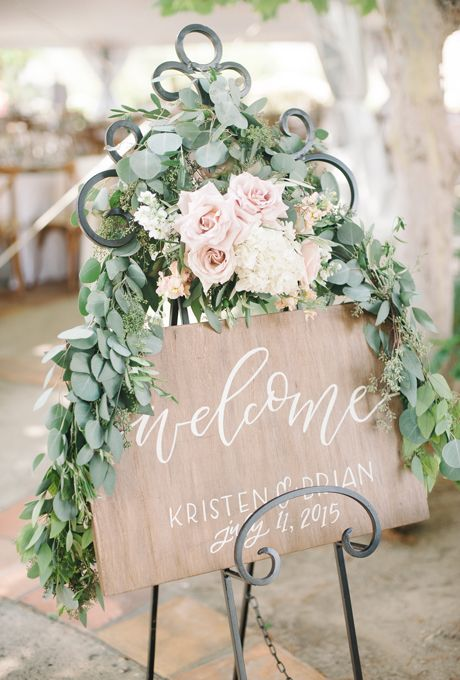 Brides.com: . Neutrals are made all the more natural with a raw wooden sign adorned with a swath of greenery and accents of blush roses and white hydrangeas.