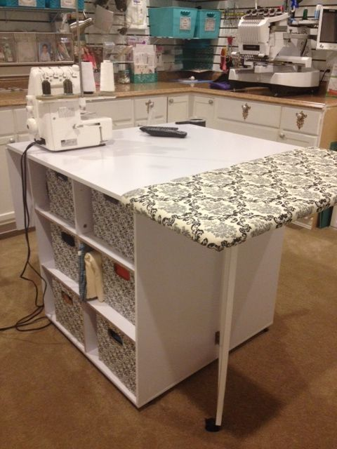 Craft countertop / table / island with storage cubes underneath and folding sides. Cover one side with padding and add ironing cover/pad over top. (Staple like uphostery.)