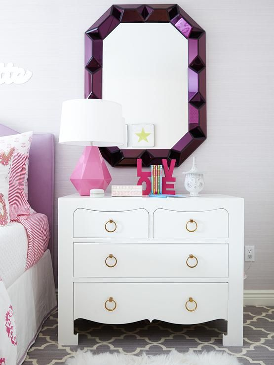 Pink and purple girl's room features light purple grasscloth on wall lined with a purple headboard on bed dressed in white and pink block print bedding and pink peace pillow next to a single nightstand, Bungalow 5 Jacqui Large 4 Drawer topped with a Robert Abbey Delta Lamp and PB Teen Love Word Bookends under a purple mirror, Bungalow 5 Romano Wall Mirror alongside a gray Moroccan trellis rug bedside mirror nightstand chest