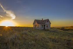 abandoned homestead in saskatchewan during sunset