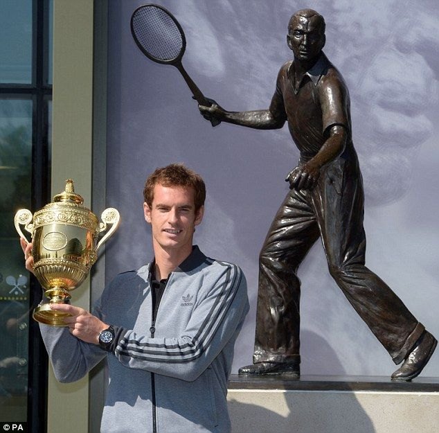 Champion: Andy Murray holds his trophy aloft outside Centre Court in front of a statue of Fred Perry - the last British man to win Wimbledon back in 1936