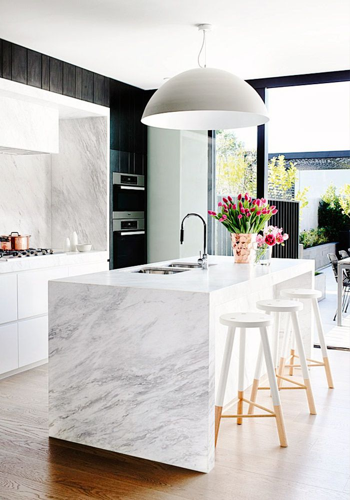 Marble kitchen with modern light fixture, beautiful flowers, and wood bar stools