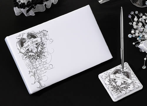 """True Love Guest Book and Pen Set  This set is covered in white satin. The 3.75"""" pen base holds a silver pen with black ink. Both the pen base and the 10"""" x 6.5"""" guest book cover are silkscreened with a black and gray design that includes leaves, vines, writing and a grunge heart with banner that reads """"True Love."""" The guest book has 30 two-sided pages for a total of 580 signatures."""