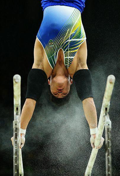 Sergio Sasaki, do Brasil, compete nas barras paralelas durante a final da equipe masculina, no terceiro dia dos Jogos Olímpicos Rio 2016