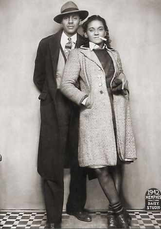 Sharp dressed couple sitting for a full length portrait shot taken at the Daisy Studio. Memphis, TN, 1942. Vintage African American photography courtesy of Black History Album.