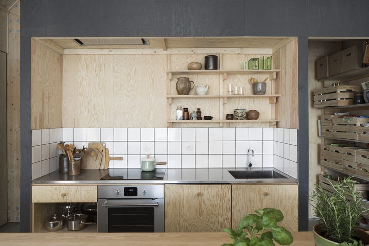 Forstberg Ling House for Mother soaring Scandinavian kitchen in natural and stained plywood with stainless counter and simple white-tiled backsplash