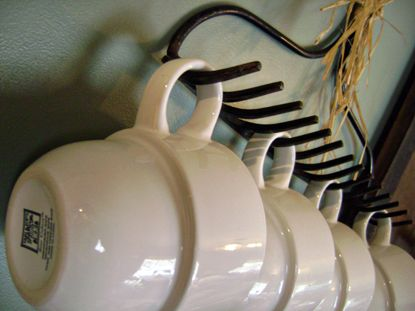 A garden rake as a cup hanger. I have 3 of these in kitchen...one for vintage knitted pot holders hanging and storage for my red handled rolling pin on top! If I find a few more...Jewelry storage in my bedroom! lol
