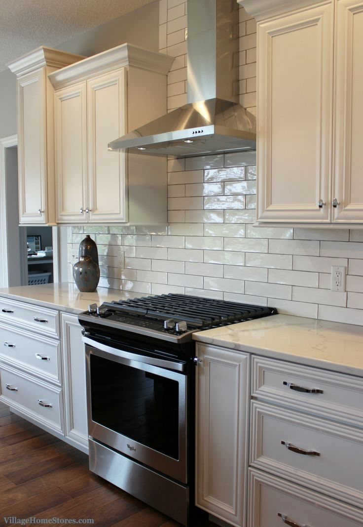 White kitchen with long subway tile Design and mat…