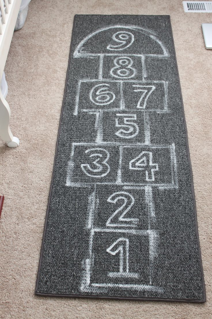 Ok...love the CB2 hopscotch rug.  Don't love the price.  So here's my version for a few hundred dollars cheaper.  Ten dollar rug painted with fabric paint to look like chalk. Done.