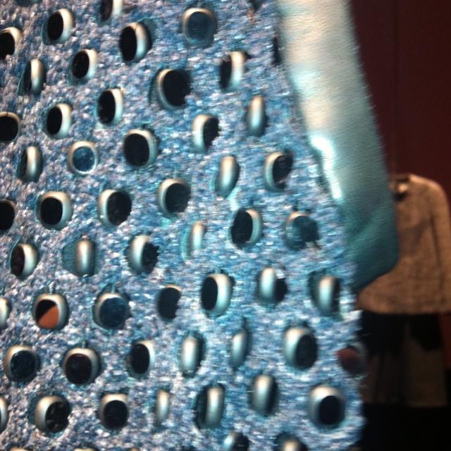 Highlight sui dettagli: lavorazioni magistrali sull'abito Calvin Klein Collection in cui le pietre piatte entrano a far parte della trama dell'abito.