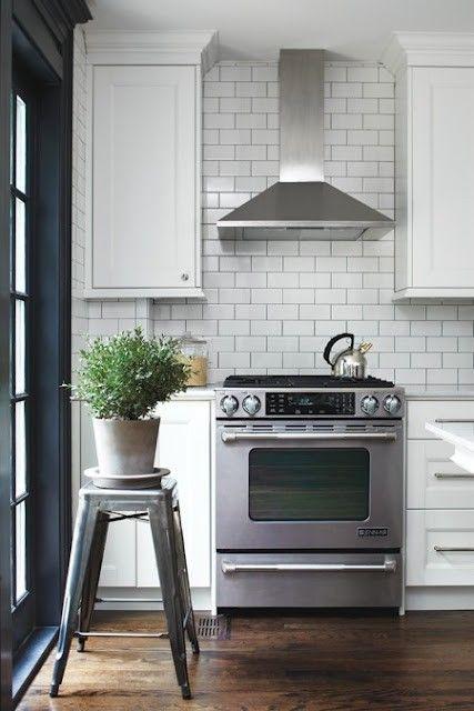 stainless steel range hood with white subway tile backsplash